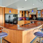 """This kitchen is a showstopper! Serious chefs will love the tools and the setting is unbeatable. Fisher and Paykel 5 burner gas range, commercial-grade hood & fan with heat/warming lamps, Dacor convection double oven. Hand-selected finishes in the kitchen enhance architectural interest: Solid wood cabinetry is installed on contrasting framework adding an artistic design edge; cabinets are Stair-Stepped in the kitchen, showcasing the sandblasted, deep-carved Native Orca etching at cooking center. Back Splash: Custom Slumped Glass, back-painted in faux marble violet, highlighted by undercounter lighting. Countertops are Black India honed-granite with accenting Red Dragon granite island/bar. Artistry continues in """"man handle"""" hardware (no longer in circulation) and suspended pendant lighting...."""