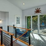 """Extensive use of glass provides maximum exposure to views and natural light. Entry is framed by both poolside and lakeside views. Heated tile floor says """"welcome home."""""""